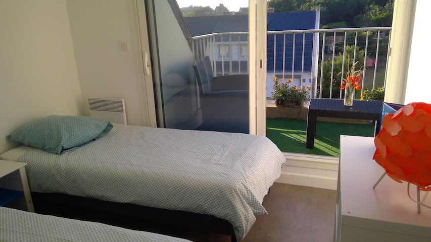 """Une deuxième chambre avec deux lits """"une personne"""" ( possibilité de les rapprocher pour faire un couchage 2 personnes). Vue mer et accès direct sur balcon."""