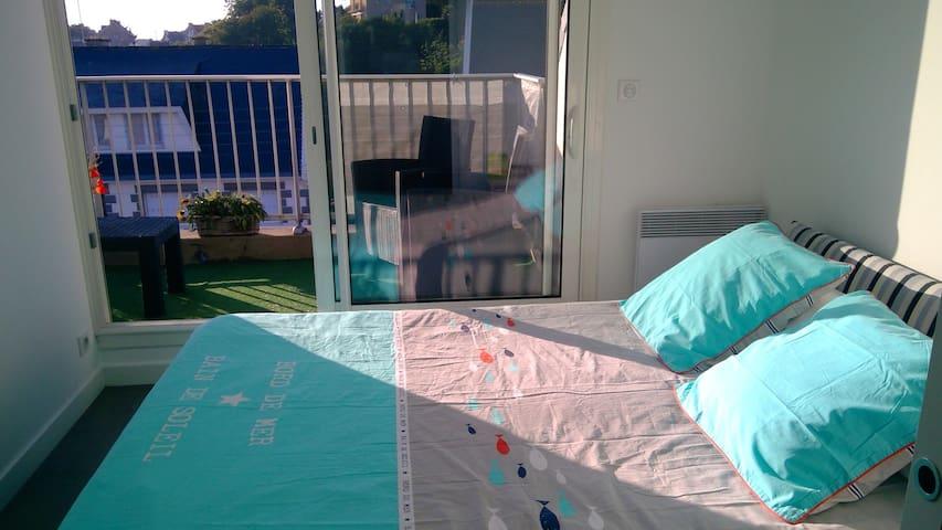 Une première chambre avec un lit double. Vue mer et accès direct à un balcon avec un salon de jardin.