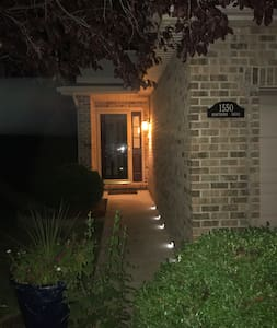 The walk to the front door is a short one from the well lit driveway.