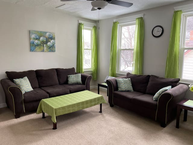 The living room features a couch and a loveseat.  There are three windows for natural light and a ceiling fan in addition to the central heating and air conditioning.  It is VERY rare to find a place with central air conditioning in this area.