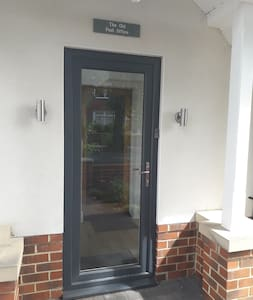 The front entrance door has outside wall lights at each side