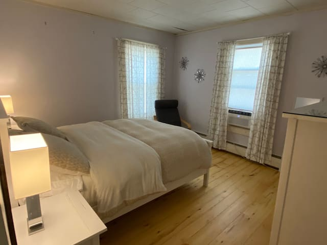 Bedroom 1 with Queen Bed and Crib with window AC unit