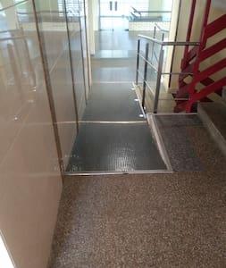 rampa de acceso al ascensor y ascensor ancho para silla de ruedas.