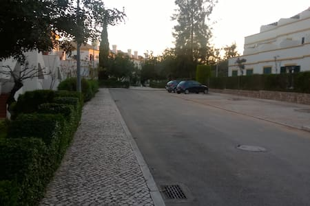 There are street lights and a sloped path to the apartment