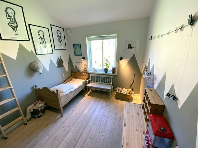 Bedroom with a small kids' bed and a loft holding a queen size bed.