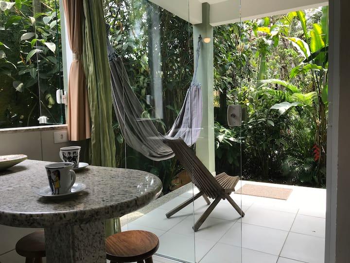 Chalé, quarto e sala, com muito verde