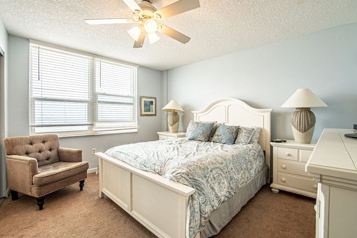 Master bedroom with ocean view, an on suite bathroom, large dresser and a comfortable chair.