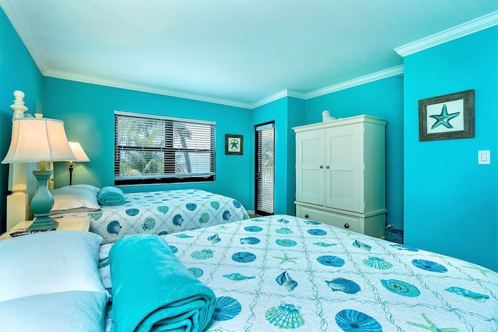 Guest bedroom with 2 Queen beds, with ocean view and balcony access.
