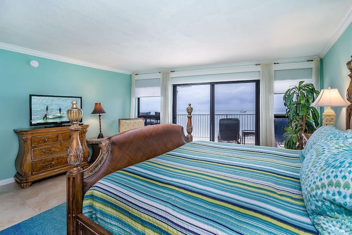 Master bedroom with king bed, TV and sliding door balcony access to ocean views.
