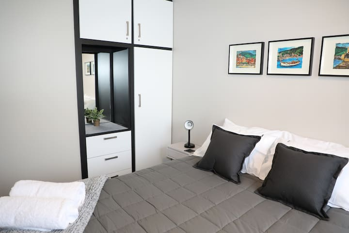 Very comfy queen bed with electric blankets next to the bathroom.