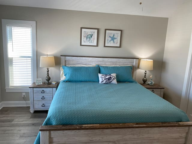 """2nd Floor King Bedroom (2nd King) with access to outside covered deck with ocean views. Also access to bathroom that can be closed and become an on-suite. Room also has a dresser, closet and 42"""" TV."""