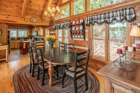 There are no hallways inside the cabin. it is an open floor plan with kitchen, bedrooms and a bathroom off of the great room. Photo shows the entry door on the right side at the far end of the dining table.  Entry bench next to the door.