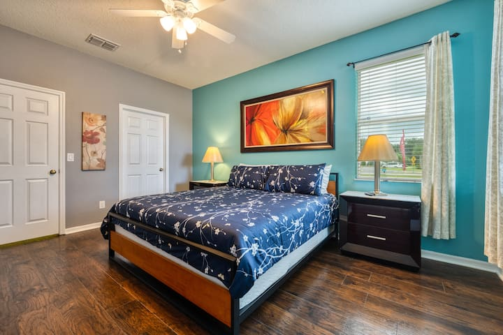 """Step Free Master Ensuite at Ground Floor with Walking in closet, Ceiling Fan, 55"""" Smart TV, dresser and nightstand."""