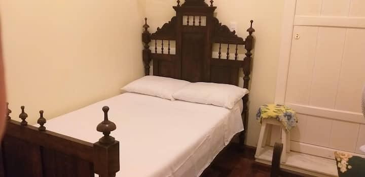 Cama viúva e sofa, ventilador e banheiro dividido