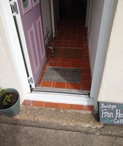 Shallow drainage channel (4cm deep) and slight threshold at the bottom of the door (4cm high) followed by two sunken door mats in the hallway. No stairs.