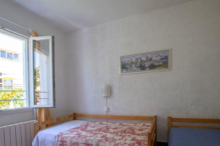Deux lits simples avec tiroirs dessous pour ranger ses affaires. La chambre donne sur le jardin