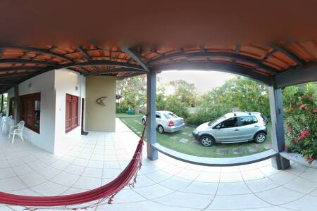 Saindo dos carros, indo ao final do estacionamento, a entrada para a varanda, seguindo até a porta principal, não há degraus.