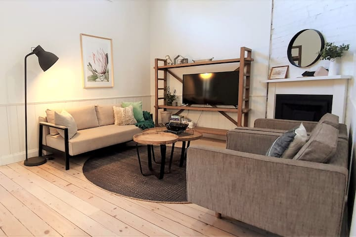 The stylish lounge features an ornamental fireplace, three-seater sofa bed and two armchairs.