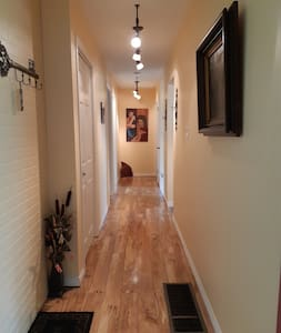hallway leads to same floor living room, dining room, kitchen, patio with screened in gazebo, both bedrooms and bathroom