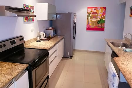Ground Level Access Includes Entry Garden, Outdoor Dining Area, Kitchen and Indoor Dining Area, Living Room (with Third Bed), and Laundry Room