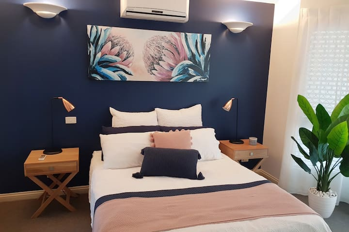 The master bedroom is fitted with a queen-sized bed, air-conditioning and wardrobe space for storing your belongings.