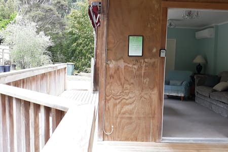 Flat entrance to lounge through ranch slider. Entrance to the bedroom has a grarail at doorway and a removable ramp.