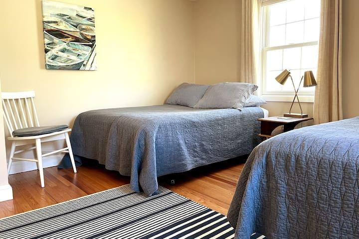 Bedroom 2: 2 double beds, A/C window unit, closet, dresser and floor fan.