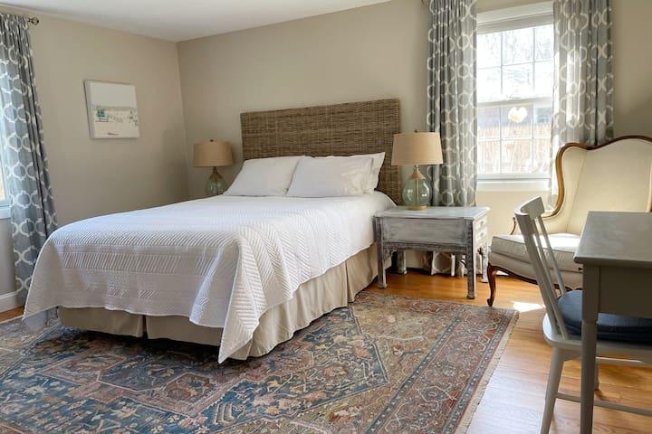Bedroom 1: Queen bed, dresser, closet, desk, reading chair, a/c window unit, floor fan.