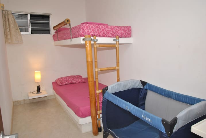 Habitación No. 7 con (2) camas sencillas. Capacidad 2 personas. Ventilador. Esta habitación comparte baño con Habitación No. 6. Acceso a la habitación zona de la lavandería