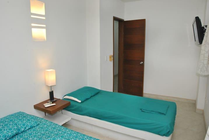 Habitación No. 6 con (2) camas sencillas. Capacidad 2 personas. TV - DIRECTV, A/A y ventilador. Esta habitación comparte baño con la habitación No. 6. Acceso a la habitación zona de lavandería.