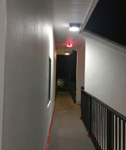 Exit the elevator to well lit railed walkway leading to condo unit