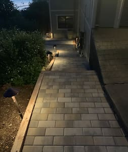 Lighted walk lights down stone walkway to Airbnb