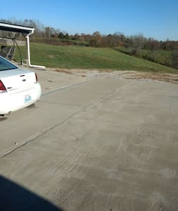 Flat concrete parking pad is level with porch and house.