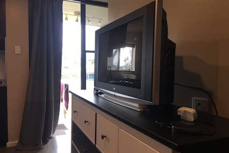 The door way has a soft full length curtain that can be easily pushed aside to allow wheelchair access into the apartment. There is a tv 60 inches away from the entrance