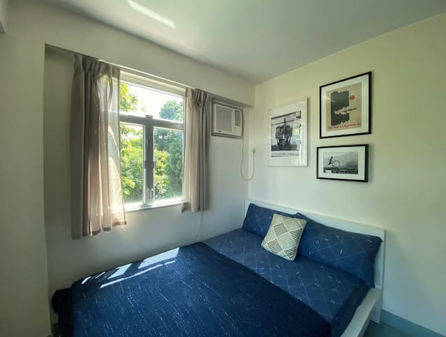 Guest room with double bed, open storage and armchair