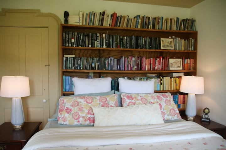Master 1st floor king bed suite. Hotel quality comfortable bed. Beautiful built-in bookshelves as your backrest. Filled with antiques, art, and books collected by the owner's Mother. Floor to ceiling french doors view the farmland and field beyond.