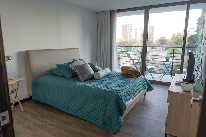 Dormitorio principal con acceso a balcón walk in closet y baño privado.