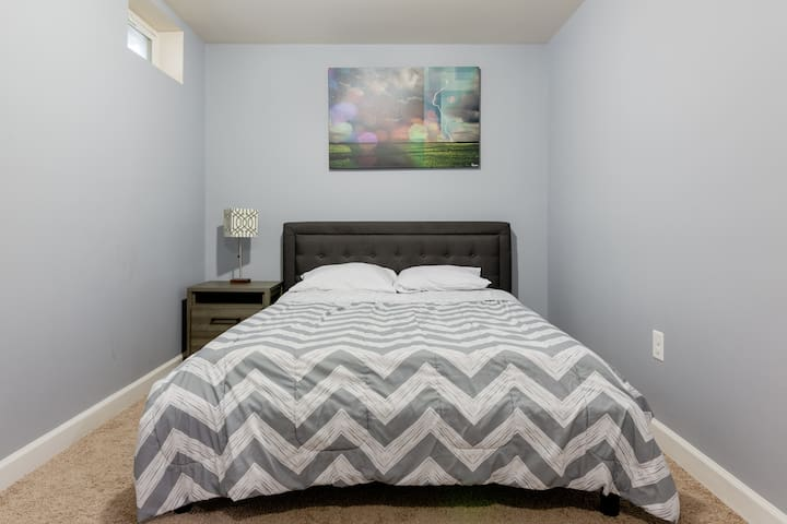 Room with queen bed and work station