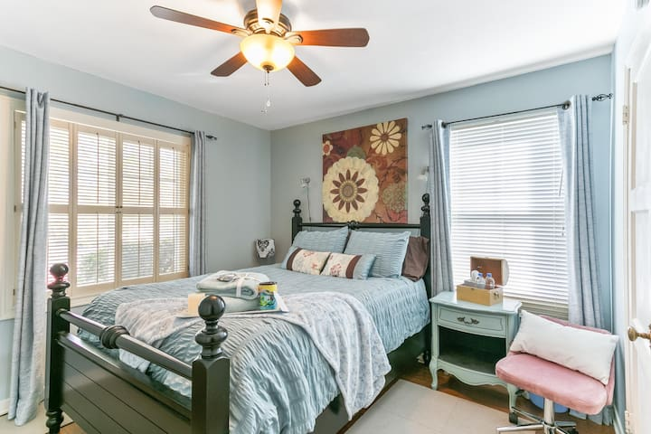Front bedroom with cooling ceiling fan, reading lights, and a comfortable queen bed.