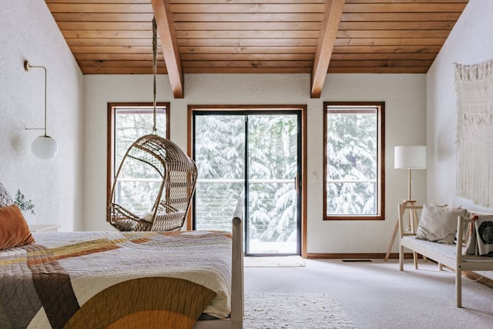 The main bedroom with hanging chair and sitting area is perfect to dive deep into a new book.