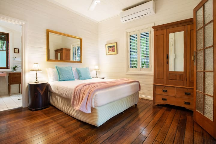 An elegant and spacious master bedroom has a queen bed, air conditioning, a stunning timber wardrobe and direct access to the bathroom.
