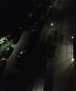 View of the buildings entrance area as seen from the balcony at night.