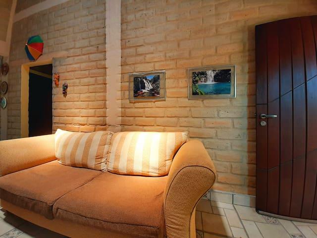 A sala possuí dois sofás e decoração dos atrativos naturais de Cavalcante.
