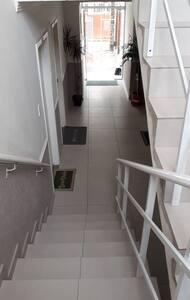 Hall de entrada linha reta, com 2 lances de escada até o apartamento