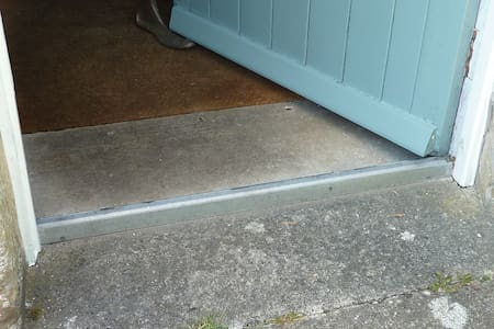 There is a metal door threshold strip about one inch high