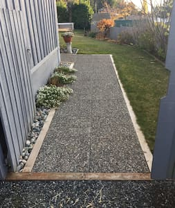 The entrance way is at the right of the house and parking at the grey gate with wide flat paving stone walkway. There is a sensor light at the walkway and the entrance.