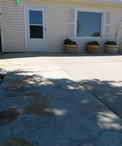 Parking is located on concrete driveway which leads to entrance door. Porch light directly above door.