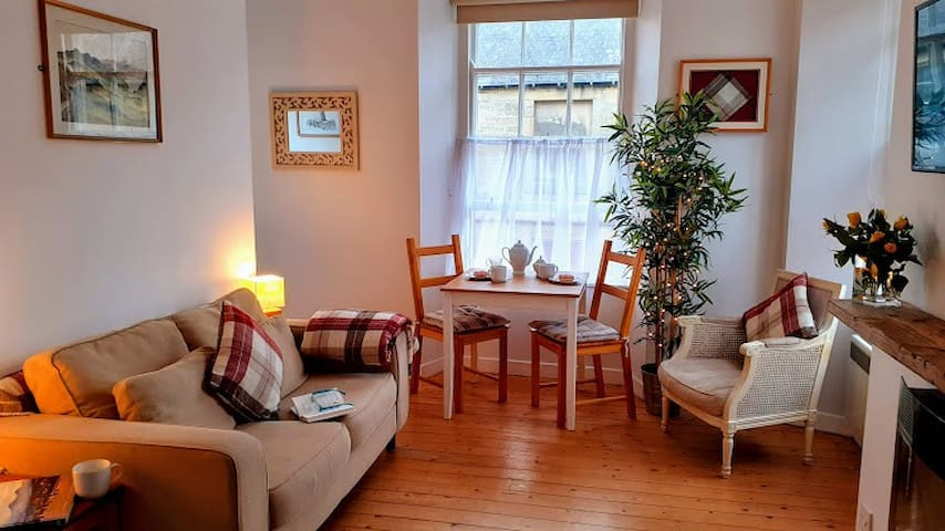 Comfortable lounge dining area. Sofa,  table for dining and or working. Additional heating from wall mounted modern flame effect fire. Chabby chic easy chairs and chunky scaffold mantle. Duel aspect windows over street with privacy curtains.