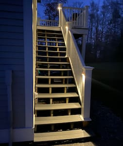 Well-lit stairs leading to apartment entrance.