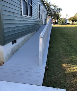 """ADA compliant ramp leading to 36"""" wide side entry door from golf cart parking pad."""